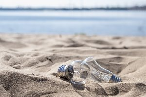 two incandescent lamps on the sand of sea beach on a summer day