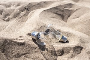 two incandescent lamps dropped on the sand on summer sunny day