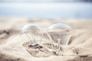 two lighting lamps burried by sand on the beach