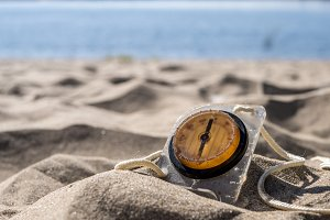 travel handy compass on the beach burried by sand