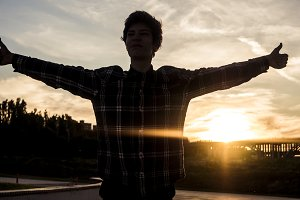 silhouette portrait of young happy man in casual showing thumbs up outside against the sunset