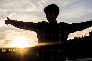 silhouette of happy successful guy showing thumbs up against the sky during sunset