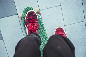 first person view of man in red sneakers riding a penny board