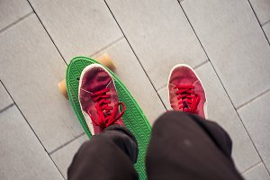 motion blur man's feet in red sneakers pull the skate riding a penny board