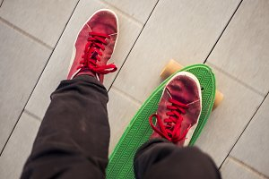 man's legs riding a penny board close up