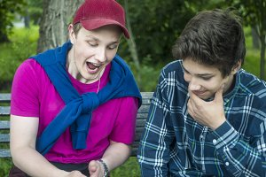 two guys outside crazy emotions staring at the phone outdoors