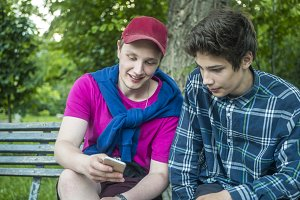 young attractive man showing the news feed on the phone to his younger brother in the park