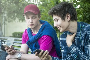 portrait of two fashionable attractive smiling guys sitting on the bench and sharing photo on the phone