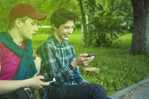 two young friends laughing looking at the modern phone sitting on the bench in the park
