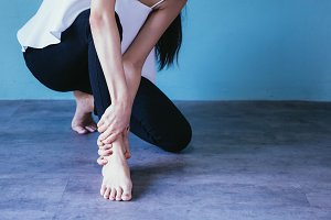 Young woman having ankle pain isolated over blue background - Healthcare and Medical concept
