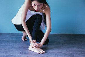 Young Asian woman having ankle pain isolated over blue background - Healthcare and Medical concept