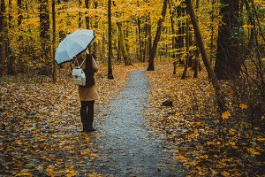 Girl with umbrella on the autumnal colorful forest path