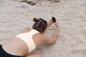 Beautiful woman taking photos on yhe knees with smart phone technology on paradise beach destination summer wanderlust vacation