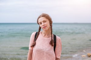 A hipster girl with braided hair in pigtails is walking along the beach in clothes. Summer concept, leisure tourism