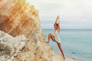 A beautiful young girl with short hair is dressed in shorts and a white jersey practicing yoga against the backdrop of the sea and mountains. Pose warrior hero. Concept about balance and calmness
