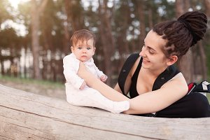 A beautiful smiling young brunette woman with long dreadlock hair hold a pretty baby. Mother looks tenderly at the child. They are in the green summer forest.