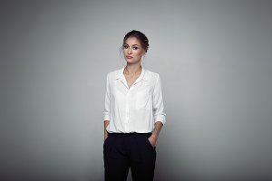 Interested businesswoman with trendy makeup posing on gray background in studio. Indoor photo of serious young lady in white blouses classic black pants standing in confident pose.