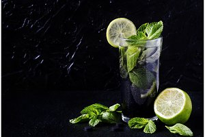 healthy mojito with activated charcoal. Detoxification and freshness. on a black background.