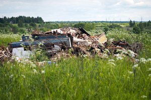 Dump garbage in the field. The concept of environmental pollution