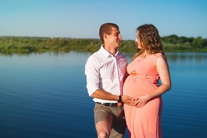 Beautiful happy pregnant couple in nature