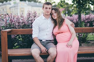 Happy young family . Pregnant young woman in pink clothes. Rest in the Park