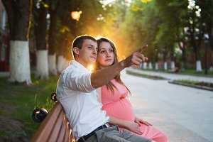 Happy young pregnant family looking to the future