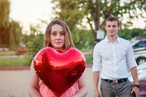 The concept of happy love. Pregnant happy young woman with heart shaped ball