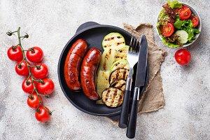 Grilled pork sausages and vegetables
