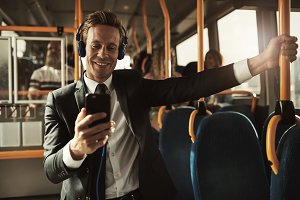 Smiling businessman listening to music while riding on a bus
