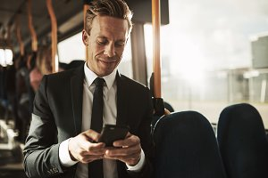 Smiling young businessman sending texts while riding on a bus