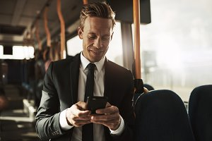 Smiling young businessman standing on a bus reading text messages