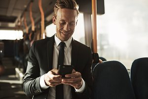 Smiling young businessman reading text messages during his morning commute