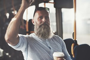 Mature bearded man standing on a bus drinking coffee