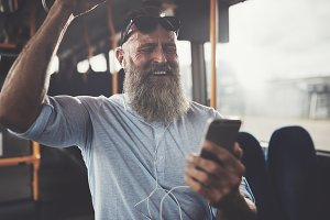 Mature man listening to music and laughing on a bus