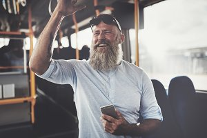 Smiling mature man riding a bus listening to music