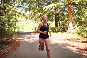 Fit young blonde woman running along a forest path