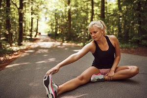 Fit young blonde woman stretching before a forest run