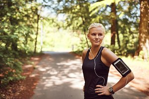 Fit young woman listeing to music before her forest run