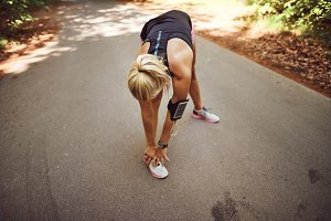 Fit woman stretching before going jogging in the forest