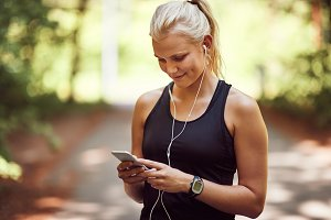 Smiling woman listening to music on earphones befor a run