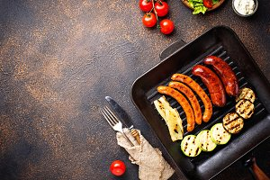Assortment of grilled  sausages and vegetables in grill pan
