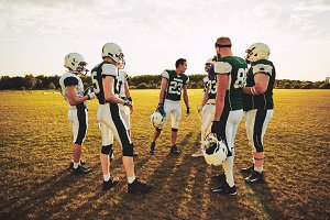 American football players discussing strategy together before a game