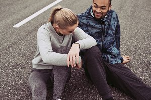 Smiling young couple sitting together on a road after running