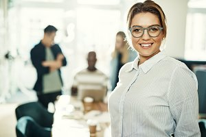 Confident young businesswoman smiling with colleagues working behind her