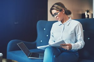 Focused young businesswoman sitting on a couch going through documents