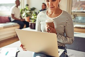 Businesswoman working online and enjoying a coffee on her break