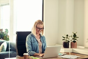 Smiling young businesswoman sitting at her desk working online