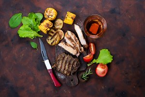 Fresh three types of grilled steak (chicken, pork, beef) on slate plate with herbs, tomato and grilled potatoes