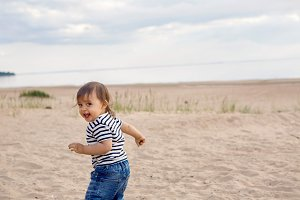 barefoot child walks on a sandy beach in a t-shirt