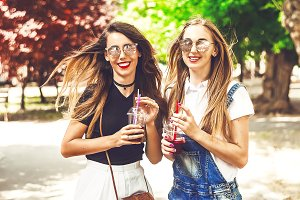 cheerful, bright girlfriends in sunglasses with a smile on her face. hair develops a wind. in the hands of juice with ice and straws. street and sunny summer day